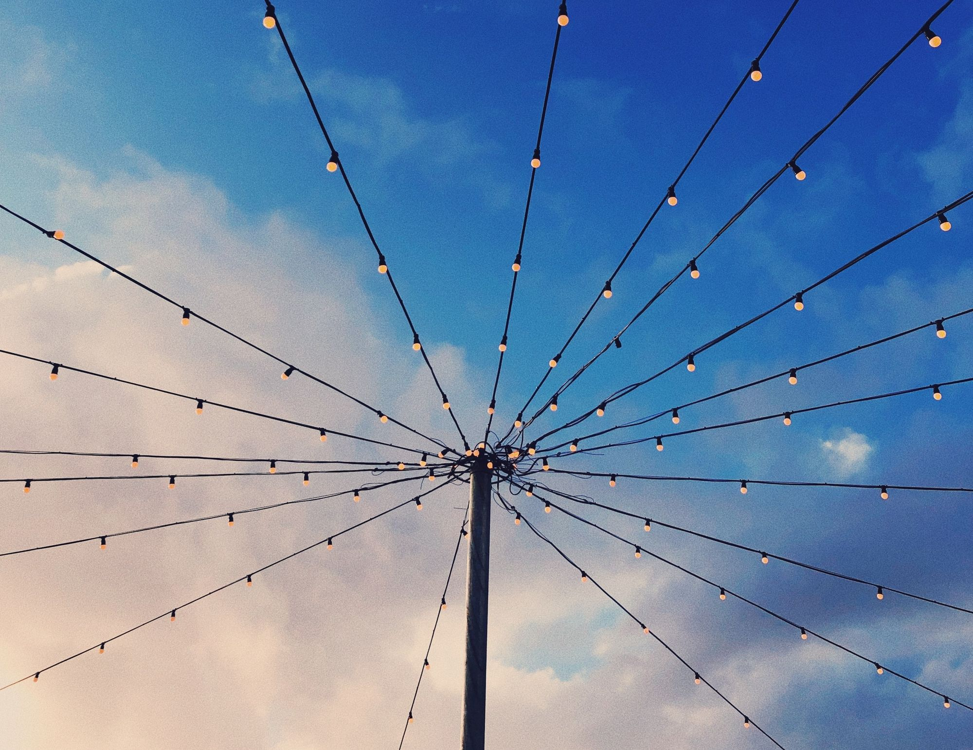An image of a telephone pole with many wires covered in lights coming from it, against a blue cloudy sky